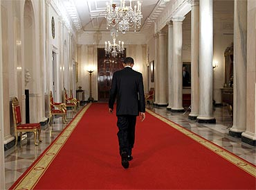 US President Barack Obama walks down the Cross Hall of the White House