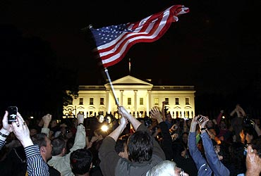 People cheer and wave US flags outside the White House