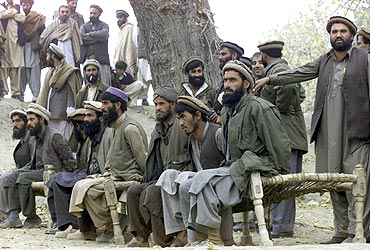 Captured Afghan Al Qaeda members sit on a bench as they are presented to the media in Tora Bora, in this file picture taken on December 17, 2001