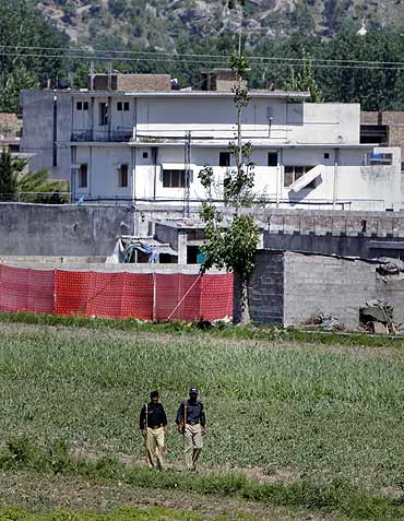 Pakistani policemen walk past Osama's compound, covered in red fabric