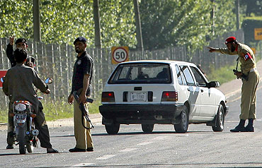 Policemen and a soldier halt traffic at a road block at Abbotabad