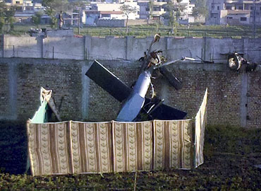 Part of a damaged helicopter is seen lying near Osama's compound
