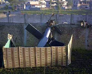 Part of a damaged helicopter is seen lying near the compound where Al Qaeda leader Osama bin Laden was killed