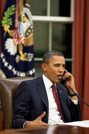 President Barack Obama talks on the phone in the Oval Office before making a statement to the media about the mission against Osama bin Laden