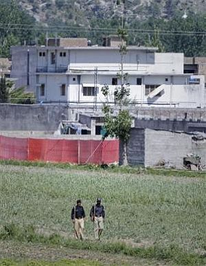 Pakistani policemen walk past a compound, surrounded in red fabric, where locals reported a firefight took place overnight