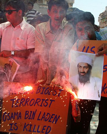 People hold placards and photographs of Al Qaeda leader Osama bin Laden as they celebrate his killing