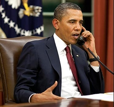 Obama talks on the phone in the Oval Office before making a statement to the media about the mission against bin Laden
