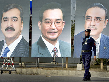 policeman walks past giant portraits of Pakistan's Prime Minister Yusuf Raza Gilani, China's Premier Wen Jiabao and Pakistan's President Zardari displayed along a road in Islamabad
