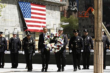 US President Obama carries a wreath during a wreath laying ceremony in tribute of 9/11 victims in New York