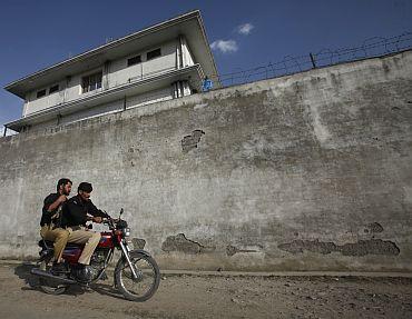 Policemen ride past the compound where Al Qaeda leader Osama bin Laden was killed in Abbottabad