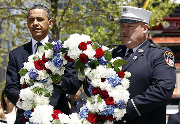 President Obama carries a wreath accompanied by a New York City firefighter at the Ground Zero site of the World Trade Center in New York