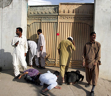 Local residents try to look past the gates into the compound where Osama bin Laden was killed in Abbottabad