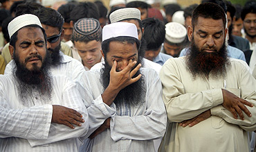 Supporters of the banned Jamaat-ud-Dawa weep while taking part in a symbolic funeral prayer for Osama bin Laden in Karachi