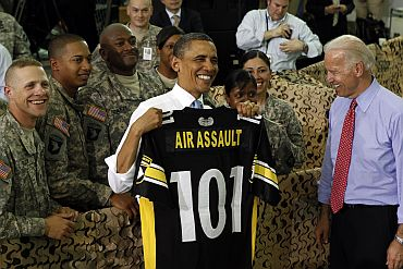 President Obama holds up a shirt for the 101 Airborne after speaking to troops at Fort Campbell in Kentucky