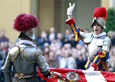 A  new recruit of the Vatican's elite Swiss Guard gestures during the swearing in ceremony at the Vatican