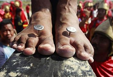 Three-inch custom made stainless steel nails pierce the feet of a penitent crucified during the Good Friday lenten rites in San Juan, San Fernando city, Pampanga province in northern Philippines April 22