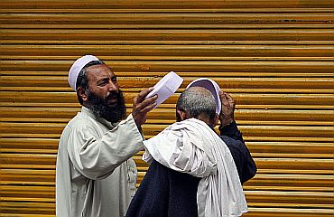 A resident tries on prayers hats for sale in Abbottabad