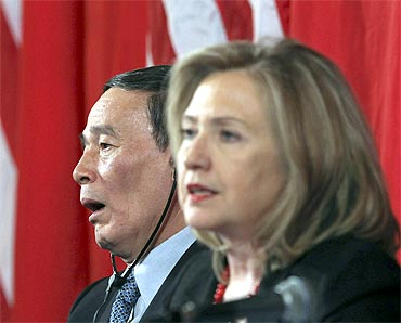 China's Vice Premier Wang Qishan (L) yawns as Hillary Clinton speaks during closing statements