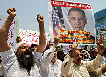 People shout anti-American slogans while holding an image of US President Barack Obama during a protest condemning the killing of Osama bin Laden