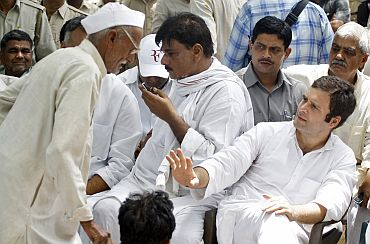 Congress leader Rahul Gandhi gestures to a villager during his visit to Parsaul village