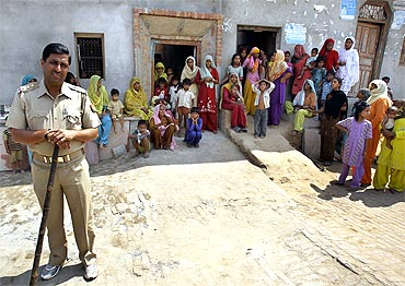 A policeman stands guard at Bhatta Parsaul village