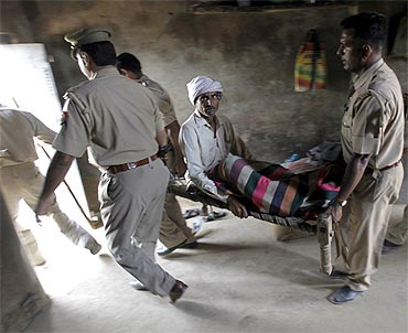 Police carry an injured man to a hospital, after Saturday's clash between farmers and police