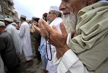 Pakistanis participate in a silent prayer after an anti-American rally in Peshawar