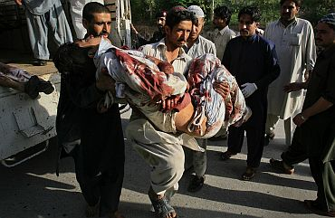 A hospital worker carries a man who was injured in a bomb attack at a paramilitary force academy in Charsadda