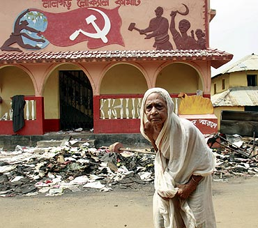 A woman walks past a damaged party office of the CPI-M at Lalgarh