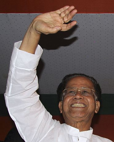 Assam CM Tarun Gogoi waves to supporters after Congress retained the state for a third consecutive term, in Guwahati on Friday