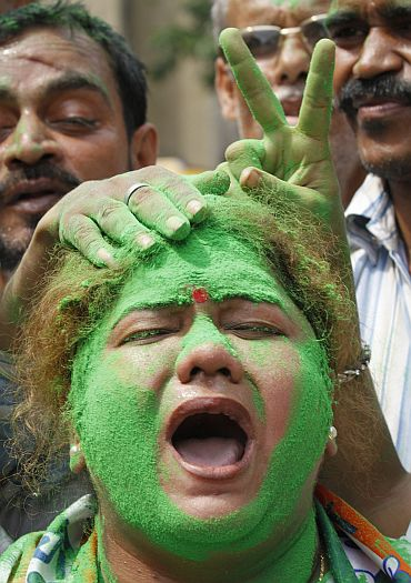 A supporter with her face smeared in green powder, a colour of the Trinamool Congress party, shouts slogans as others show the victory sign on a street in Kolkata