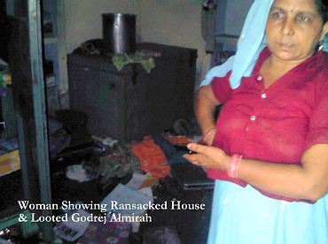 A woman shows her ransacked house