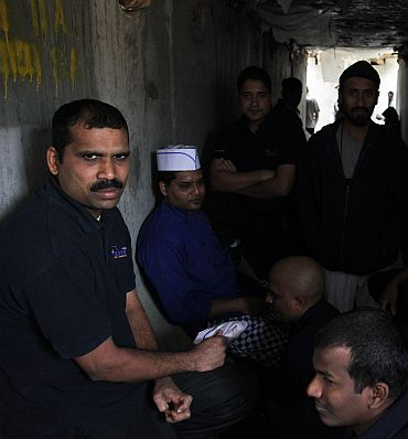 Indian foods service workers stand inside a bunker during a rocket attack by anti-Afghan forces at Forward Operation Base Joyce