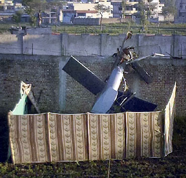 Part of a damaged helicopter is seen lying near Osama's mansion