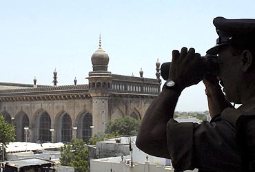 A cop keeps watch during Friday prayers at Mecca Masjid