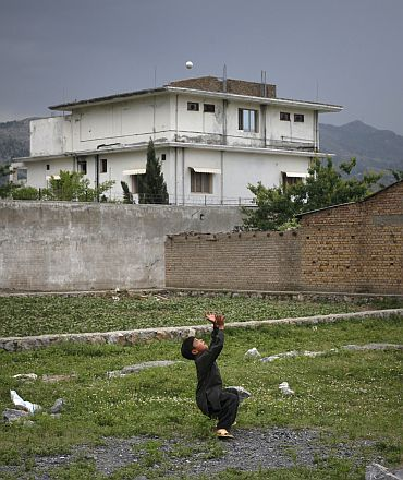 A boy plays with a tennis ball in front of the compound where US Navy SEAL commandos killed Al Qaeda