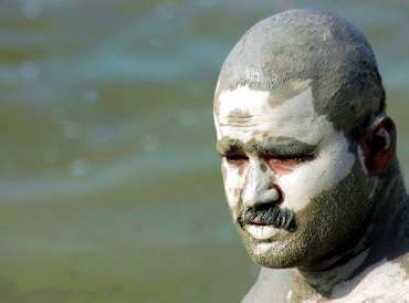 A man cools himself with mud on his body on the banks of the Ganga in Allahabad