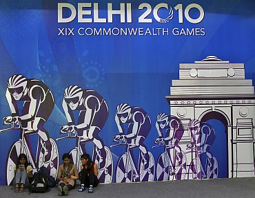 Volunteers sit in front of a board advertising the 2010 Commonwealth Games in New Delhi