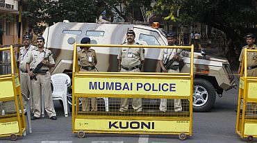 Police officers block a road with an armoured personnel carrier in Mumbai