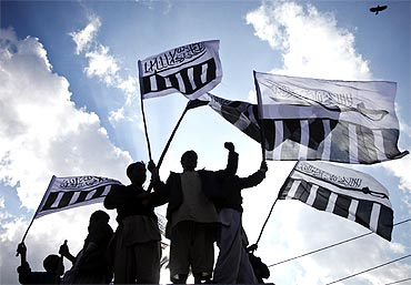 Supporters of Jamaat-ud-Dawa, the frontal outfit for Lashkar-e-Tayiba, hold their party flags