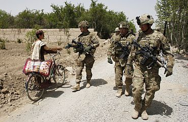 U.S. Army soldiers shake hands with a local youth as they walk near Combat Outpost Nolen in the Arghandab Valley, Kandahar