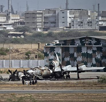 Officials stand near a damaged aircraft at the PNS Mehran base