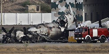 A fire truck is parked near a damaged aircraft at the Mehran naval aviation base after troops ended operations against militants in Karachi