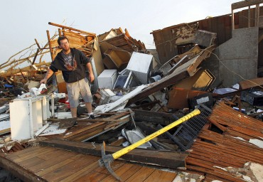 A man sorts through the debris looking for personal belongings after his home was destroyed