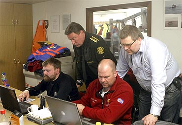 Emergency personnel work at the temporally headquarters at the Geirland farm