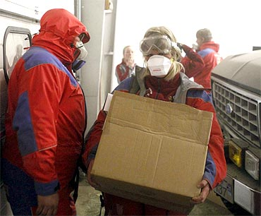 -Emergency workers carry supplies at the Geirland farm near Kirkjubaejarklaustur