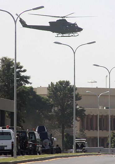 A military helicopter flies overhead as security forces surround a white van used by gunmen during an attack on the Pakistan army headquarters in Rawalpindi