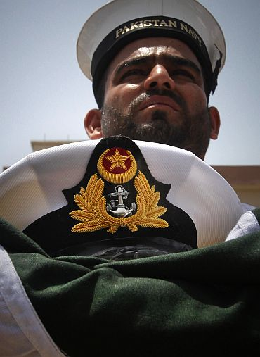 A member of the Pakistan Navy holds a national flag and a hat of navy officer Lieutent Yasir Abbas, who was killed during a gun battle against militants at the Mehran naval aviation base in Karachi a day earlier, after his burial in Lahore on May 24