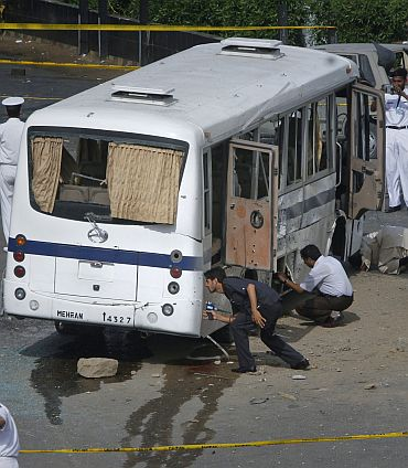 Security officials examine a bus after it was damaged by a bomb in Karachi April 28