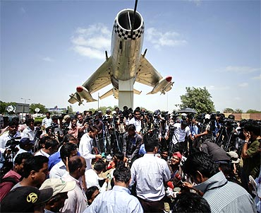 Media personnel gather at the gates of the Mehran naval aviation base after troops ended operations against militants in Karachi